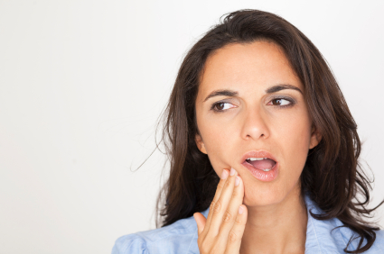 Brunette woman holding her jaw in pain at River's Edge Dental in Great Falls, MT